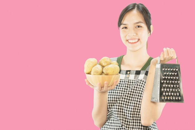 Happy lady holding kitchen stuff over copy space background