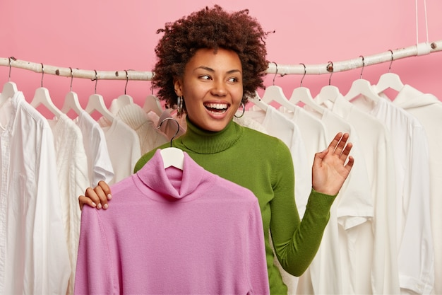 Happy lady holds new jumper on hangers, keeps hand raised, smiles broadly, looks aside, white clothes hanging in row behind.
