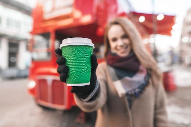 通りに立って、背景と赤いバスの通りにコーヒーの緑のカップを手で保持しているコートを着た幸せな女性
