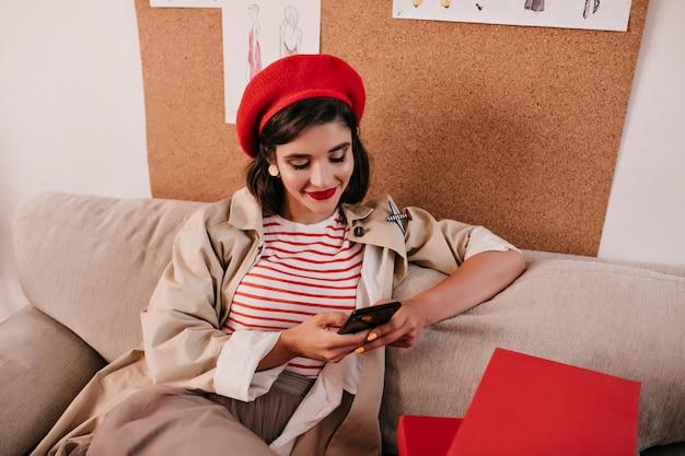 彼女のスマートフォンでチャットしている明るいベレー帽の幸せな女性。モダンな服を着たかなり美しい女性がソファに座って笑っています。