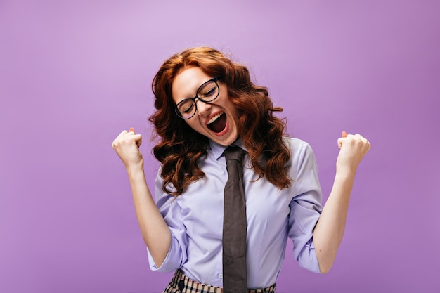 비즈니스 스타일 복장의 해피 레이디는 보라색 벽에 감정적으로 포즈를 취합니다.