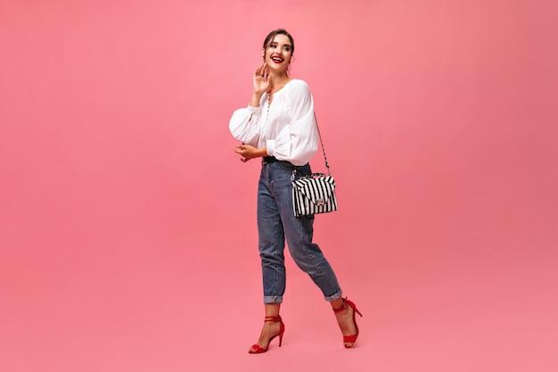 ピンクの背景にポーズをとるジーンズと白いブラウスの幸せな女性。赤い口紅とモダンな服装でブルネットの笑顔が動きます。