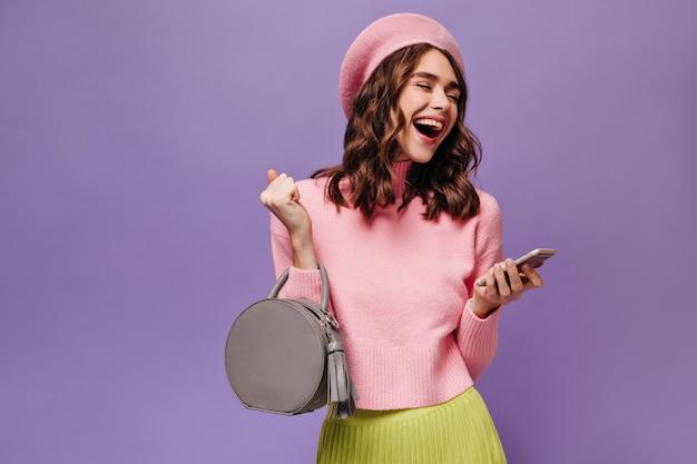 분홍색 베레모, 스웨터, 녹색 치마를 입은 행복한 여성은 미소를 지으며 전화로 메시지를 읽습니다.
