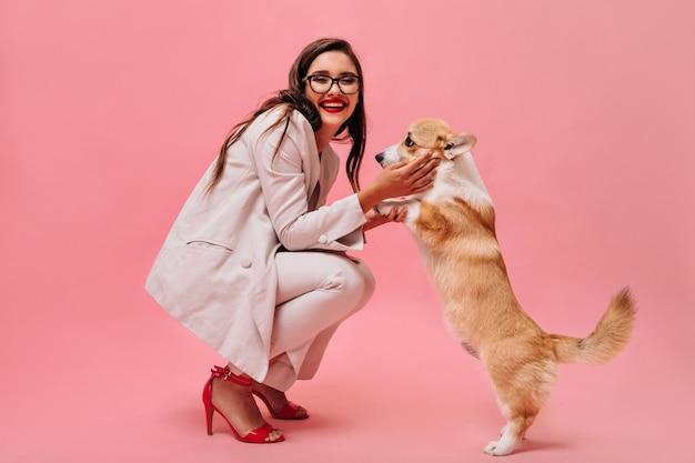 彼女の犬と一緒に楽しんでいるスーツと眼鏡の幸せな女性。明るくファッショナブルな服を着たうれしそうな女性は、孤立した背景にかわいいコーギーで遊ぶ。