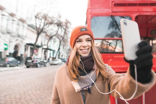 通りを背景に赤いバスの近くに立っている暖かい服を着て幸せな女性は笑顔し、スマートフォンで自撮りを取る
