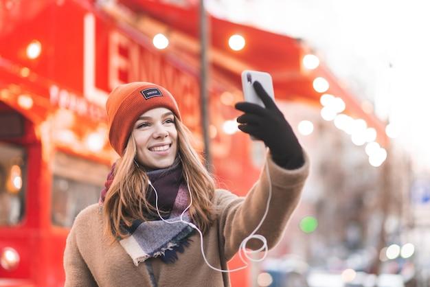 Счастливая дама в теплой одежде стоит возле красного автобуса на фоне улицы улыбается и делает селфи на смартфон