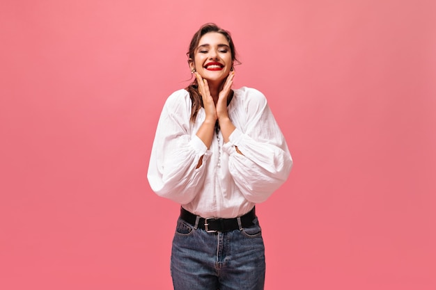Happy lady in jeans and white shirt smiling on pink background.  cheerful beautiful woman with dark hair in fashionable dress looks at camera.