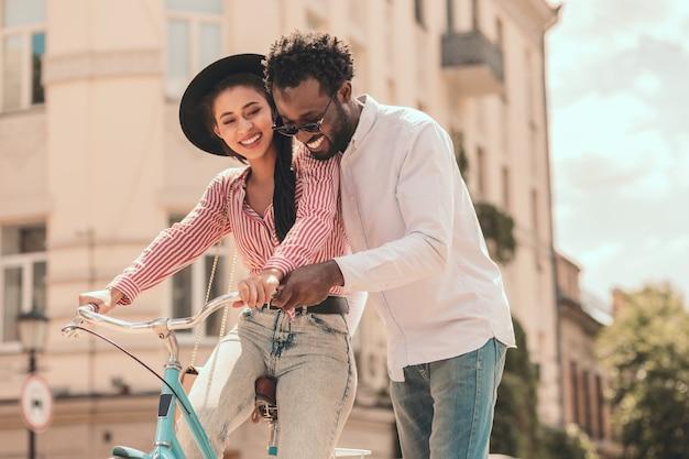 自転車に乗っている幸せな女性と彼女が乗るのを手伝っている男