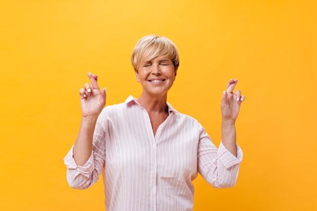Felice signora in abito rosa incrocia le dita su sfondo isolato