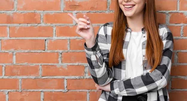 Happy lady pointing at brick wall