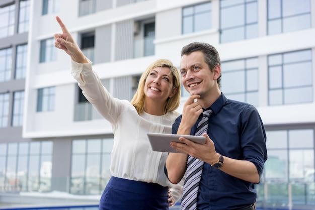 Happy lady pointing and showing male colleague something outdoors.