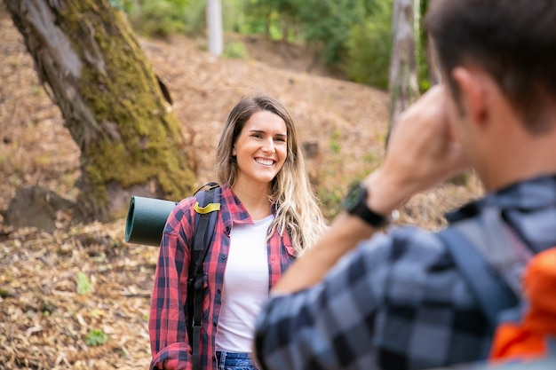 Счастливая дама позирует и улыбается на дороге в лесу. до неузнаваемости мужчина фотографирует свою девушку. туристы вместе ходят в лес и веселятся. концепция туризма, приключений и летних каникул