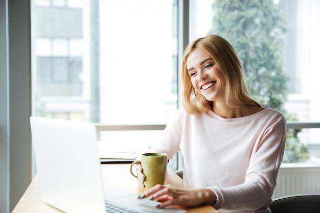 Счастливый леди, сидя в офисе коворкинг при использовании портативного компьютера