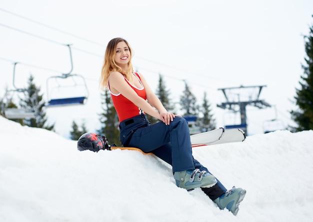 山の冬のスキーリゾートでスキー用具と雪の斜面の上に休んで幸せな女性スキーヤー