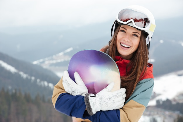 Happy lady snowboarder on the slopes frosty winter day holding snowboard in hands