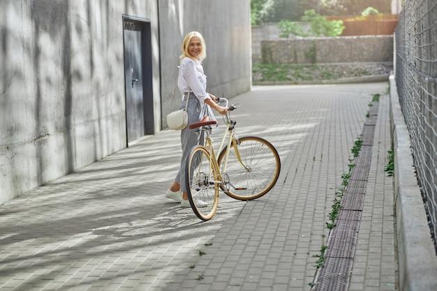 직장에 가는 동안 대도시에서 자전거로 생태 교통을 이용하는 행복한 여성