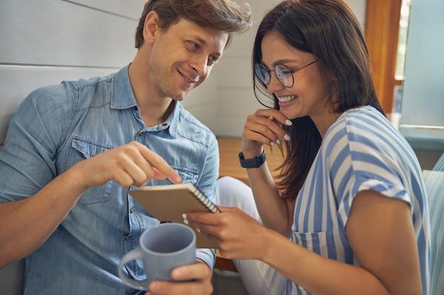 행복한 아가씨 안경을 쓰고 캐주얼 의류에 웃는 남성 커피 한모금에서 대화