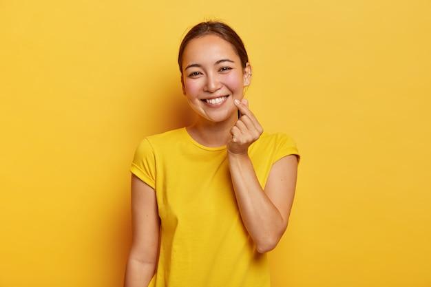 Счастливая женщина с азиатской внешностью делает корейский знак, одетая в повседневную желтую футболку, с дружелюбным выражением лица стоит в помещении. монохромный снимок. язык тела. женщина выражает любовь жестом