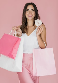 Happy lady with shopping bags and a donut