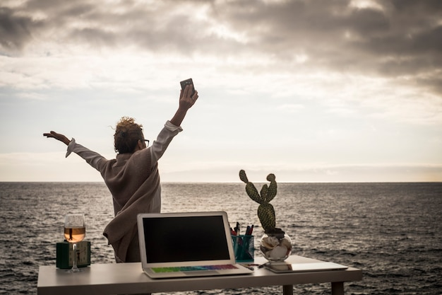 壁や制限のない代替の無料オフィスで、海の近くで屋外で働く幸せな女性