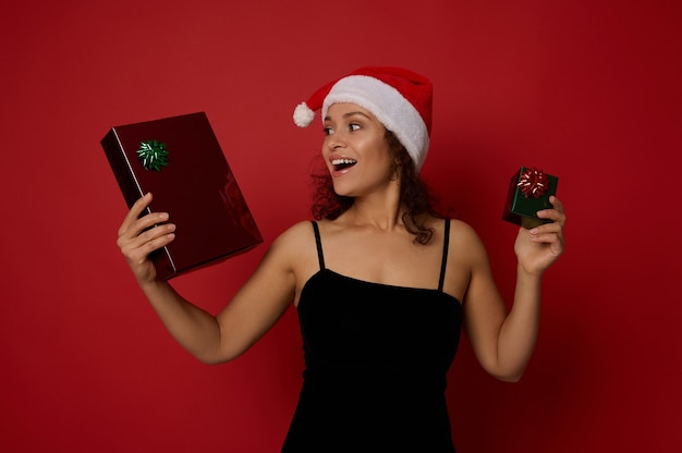 이브닝 드레스와 산타클로스에 아름다운 이빨 미소를 가진 행복한 라틴 아메리카 여성은 크리스마스 선물을 들고 빨간색 배경에 포즈를 취하는 것을 기뻐합니다. 광고 복사 공간이 있는 새해 복 많이 받으세요 개념