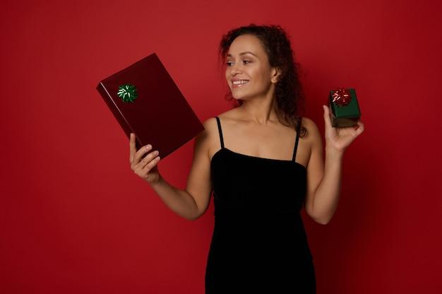 아름다운 이빨 미소를 가진 행복한 라틴 아메리카 여성은 이브닝 드레스를 입고 크리스마스 선물을 들고 빨간색 배경에 포즈를 취하는 것을 즐깁니다. 광고 복사 공간이 있는 메리 크리스마스와 새해 복 많이 받으세요 개념