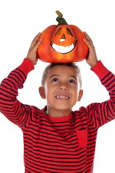 Happy latin boy holding a big pumpkin