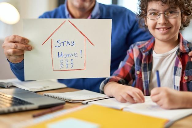 自宅で遠隔教育中に父親と一緒に机に座っている幸せなラテン系の少年。外出禁止令を持っているお父さん。オンライン教育、ホームスクーリングの概念