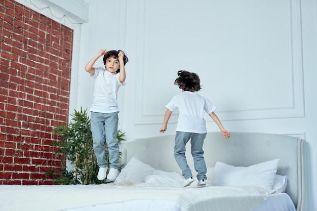 행복한 라틴 소년들, 어린 형제들이 함께 즐겁게 놀고, 집에서 침대에서 뛰어오르고 있습니다. 어린이, 행복, 가족 개념