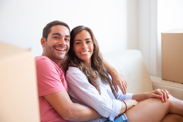 Happy latin couple sitting on couch among carton boxes in new house, looking at camera, smiling, laughing