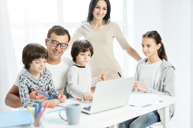 집에서 함께 시간을 보내는 아이들과 함께 행복한 라틴 가족. 아버지는 아이들이 노는 것을 보고, 집에서 일하는 동안 그림을 그리며 노트북을 사용합니다. 기술, 가족 개념입니다. 선택적 초점