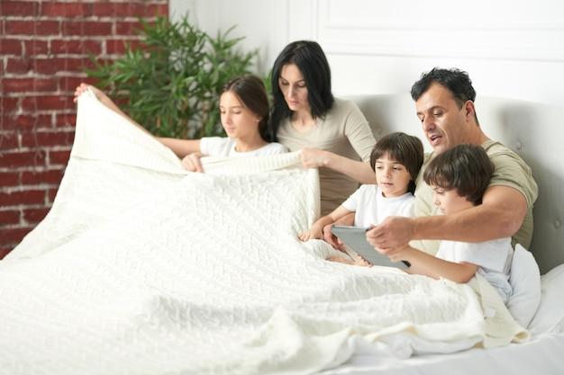 아침에 함께 침대에 머물고 있는 아이들과 함께 행복한 라틴 가족. 태블릿 pc를 사용하는 아버지, 두 명의 어린 아들과 놀고 있습니다. 어린 시절, 아침 개념