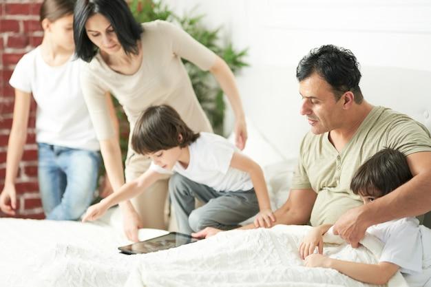 아침에 태블릿 pc를 사용하는 귀여운 아이들과 함께 행복한 라틴 가족. 사랑하는 부모는 아이들과 함께 놀고 침대에 누워 있습니다. 행복한 어린 시절, 기술 개념