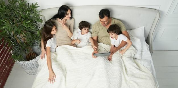 아침에 태블릿 pc를 사용하는 귀여운 아이들과 함께 행복한 라틴 가족. 사랑하는 부모는 만화를 보고, 아이들과 함께 놀고, 침대에 누워 있습니다. 행복한 어린 시절, 기술 개념