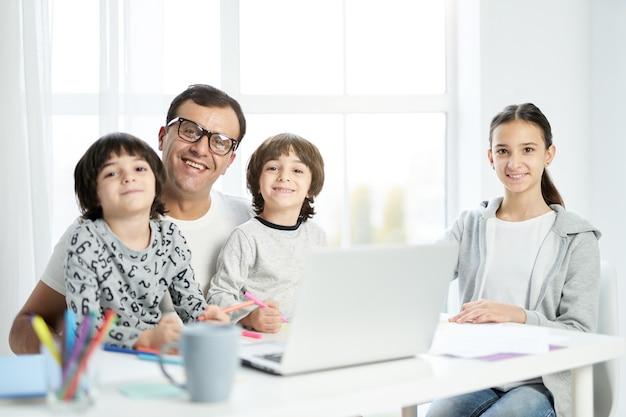 행복한 라틴계 아버지와 아이들이 카메라를 보며 웃고 집에 있는 테이블에 함께 앉아 있습니다. 노트북을 사용하고 집에서 일하고 아이들을 지켜보는 남자. 프리랜서, 가족 개념