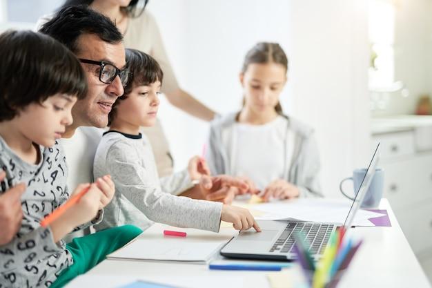 행복한 라틴 아버지는 집에서 가족과 시간을 보내는 동안 아침에 아이들과 함께 만화를 보고 있습니다. 집에 머물고, 행복한 가족, 부모로서의 개념. 측면보기