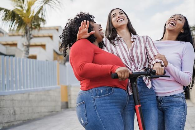 Счастливые латинские друзья развлекаются с электрическим самокатом на открытом воздухе в городе - фокус на лице девушки в центре