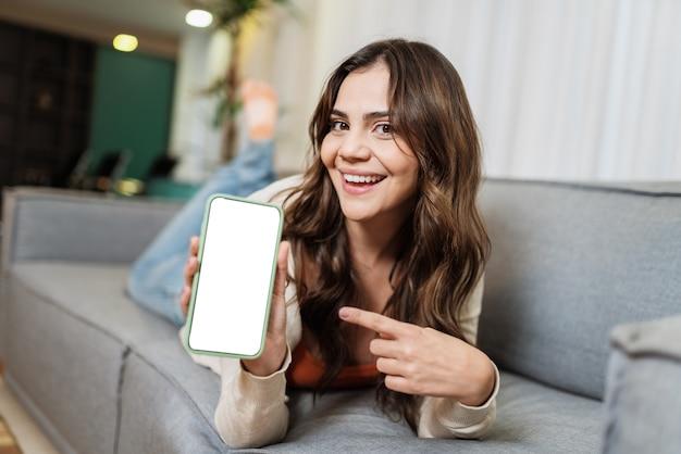행복한 라틴 여성은 휴대전화를 통해 소셜 미디어에서 좋은 소식을 공유하는 방 포즈로 집에서 혼자 휴식을 취합니다. 웃는 여자 가리키는 전화 앱.