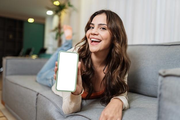행복한 라틴 여성은 휴대전화를 통해 소셜 미디어에서 좋은 소식을 공유하는 방 포즈로 집에서 혼자 휴식을 취합니다. 전화 앱을 보여주는 웃는 여자.