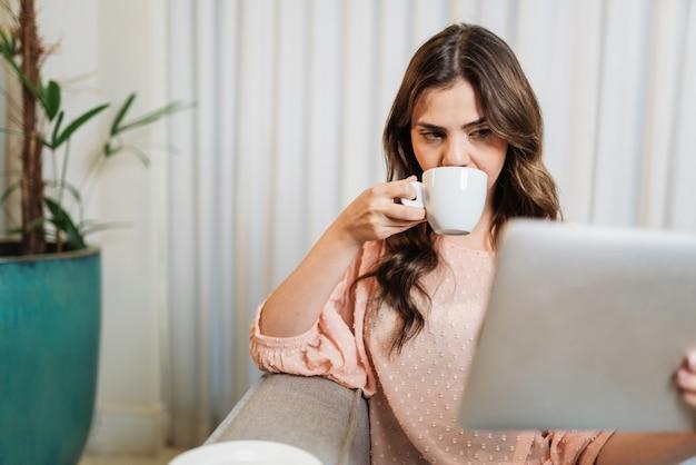 행복한 라틴 여성은 집에서 혼자 디지털 태블릿을 사용하여 방에 앉아 커피를 마시며 휴식을 취합니다.