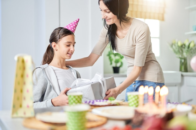 행복한 라틴계 어머니는 사랑스러운 딸에게 선물 상자를 주고 집에서 아이의 생일을 축하하면서 인사합니다. 선택적 초점입니다. 가족, 축하 개념