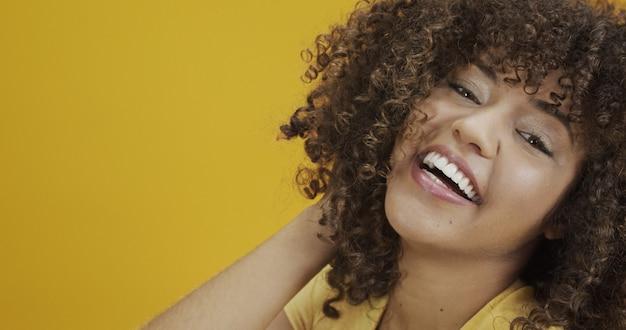 노란색 배경에 곱슬머리를 한 행복한 웃고 있는 미국 아프리카 여성. 그녀의 머리를 만지고 카메라를 보고 스웨터에 곱슬 여자 웃 고.