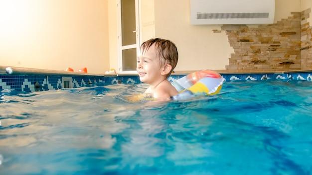 Счастливый смеющийся и улыбающийся маленький мальчик играет с игрушками и учится плаванию в закрытом бассейне