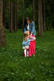 행복한 웃고 있는 여자 아이는 공원의 잔디에 서 있는 엄마를 안고 있다