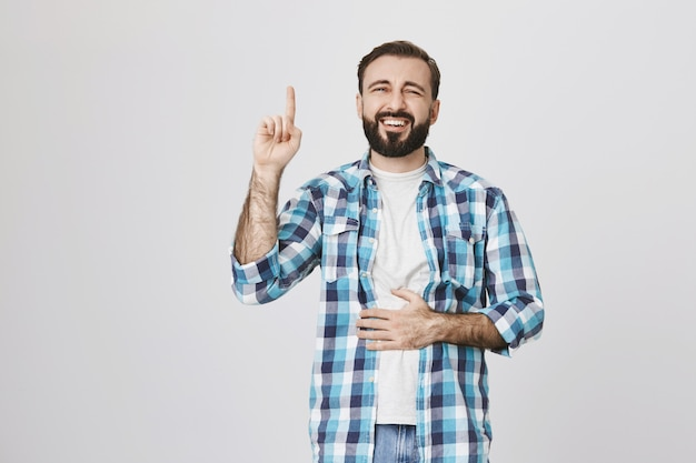 Happy laughing bearded guy pointing finger up