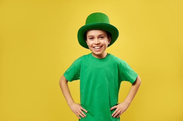 レプラコーンの緑の帽子をかぶって幸せな笑いの少年は黄色の表面でカメラにポーズをとる