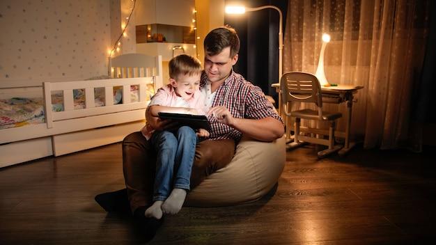 夜の寝室に座って、タブレットコンピューターでゲームをしている若い父親と一緒に幸せな笑いの少年。夜に一緒に時間を過ごす子供の教育と家族の概念。