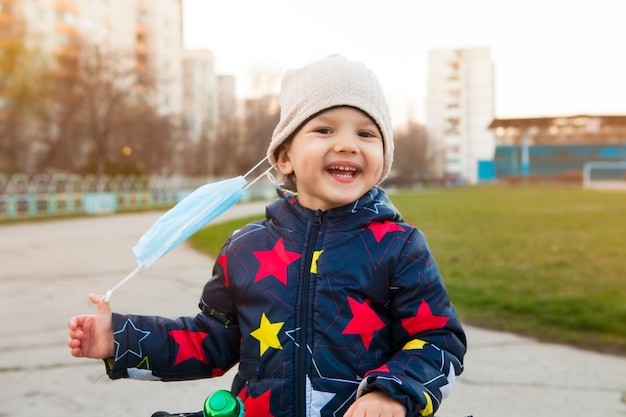 Happy and laughing child on a walk in a city park removes a medical mask from his face.