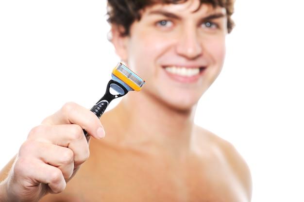 フォアグラウンドで手にかみそりを持つ若い男の幸せな笑いきれいに剃った顔