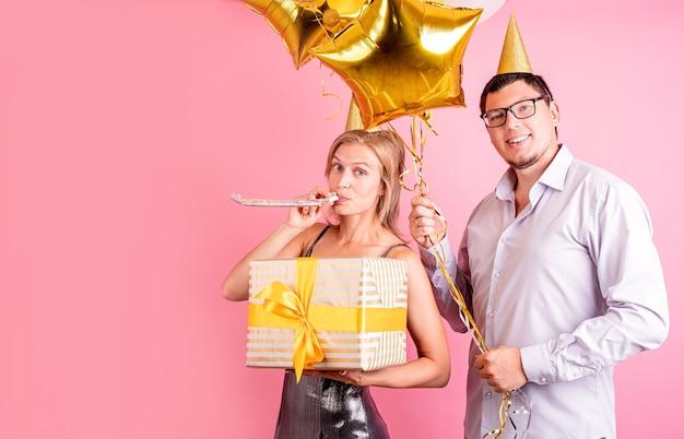 ピンクの背景に分離された金色の風船とギフトボックスを保持している誕生日パーティーを祝う幸せな笑いカップル